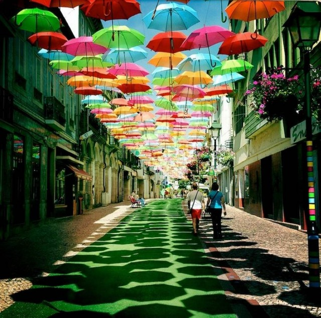 In Águeda, Portugal some streets are decorated with colorful umbrellas protecting walkers from the summer sun.