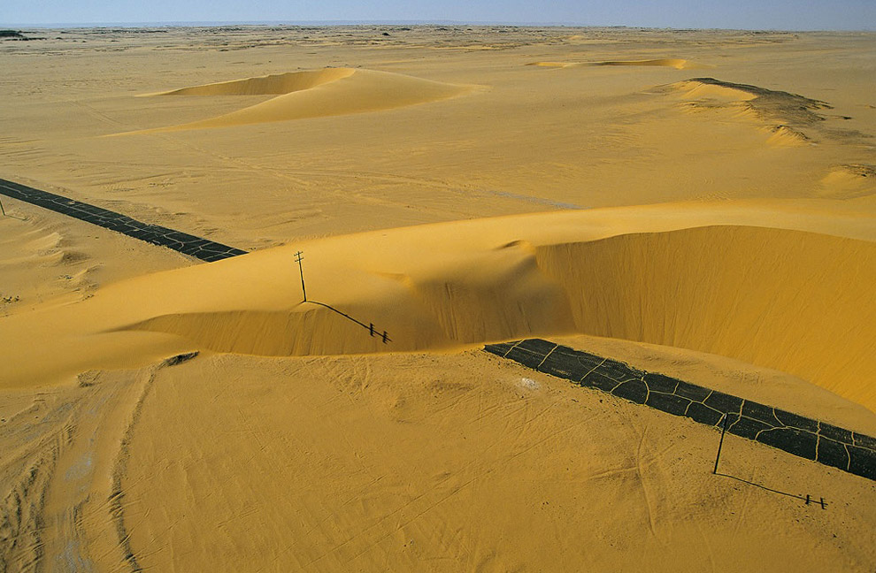 Road interrupted by a sand dune, Nile Valley, Egypt. Dunes cover nearly one-third of the Sahara, and the highest, in linear form, can attain a height of almost 1,000 feet (300 m). Barchans are mobile, crescent-shaped dunes that move in the direction of the prevailing wind at rates as high as 33 feet (10 m) per year, sometimes even covering infrastructures such as this road in the Nile Valley.