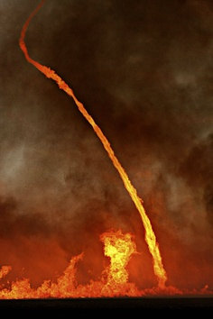 A fire whirl, known to some as the fire tornado.  occurs when intense rising heat and turbulent wind conditions combine to form whirling eddies of air. These eddies can tighten into a tornado-like structure that sucks in burning debris and combustible gases.