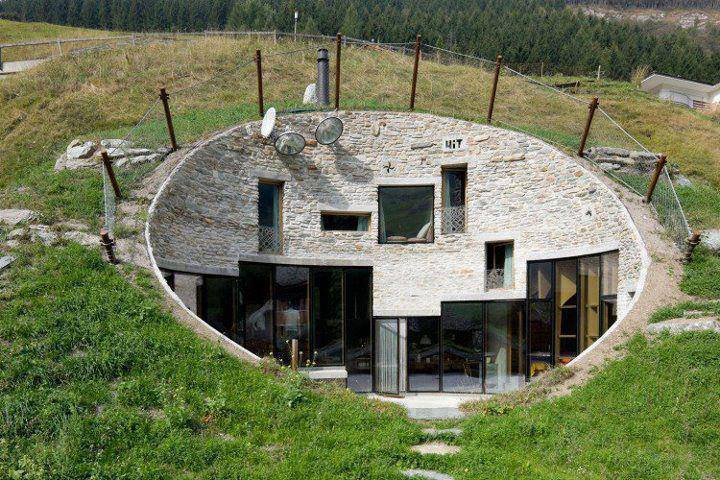 Underground home in Switzerland constructed of concrete, oak doors and features an outdoor terrace complete with a spa, barbecue, dining area and a stunning view of the Alps. The front entrance is used when receiving company, while an underground tunnel provides family members access to the barn from the rear.