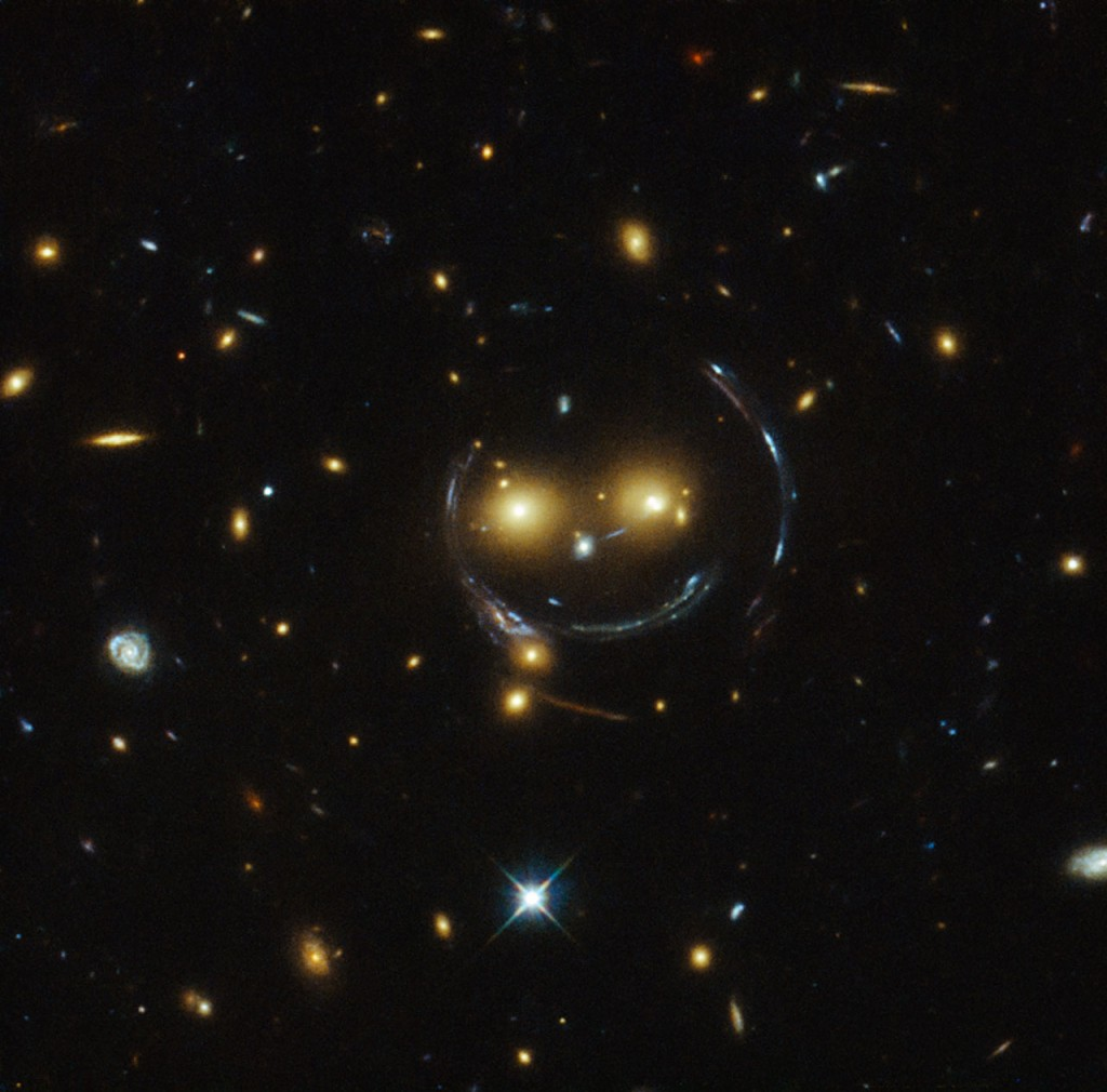 "In the centre of this image, taken with the NASA/ESA Hubble Space Telescope, are two faint galaxies that seem to be smiling.   You can make out two orange eyes and a white button nose. In the case of this ""happy face"", the two eyes are the galaxies SDSSCGB 8842.3 and SDSSCGB 8842.4 and the misleading smile lines are actually arcs caused by an effect known as strong gravitational lensing.  Further explanations here talks about ""such a powerful gravitational pull that they can warp the spacetime""  Too much for me.  :)"