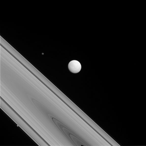 The Saturnian moons of Titan, Hyperion and Prometheus are visible just beyond the planet's trademark rings in a photo captured by Cassini space craft on July 14, 2014.