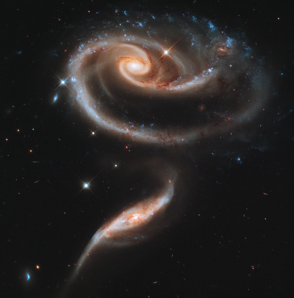 A rose made of a pair of interacting galaxies, released to celebrate the 21st anniversary of the launch of the NASA/ESA Hubble Space Telescope. The distorted shape of the larger of the two galaxies shows signs of tidal interactions with the smaller of the two. It is thought that the smaller galaxy has actually passed through the larger one.