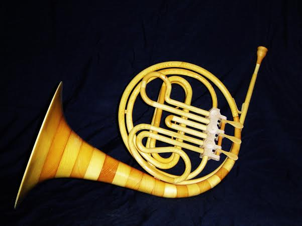 "This French Horn is made from scrap pieces.   The wood is turned to a 1/16"" .   The wood is turned to 1/16"" thickness, so that all the tubing is hollow and it can be played. By Murray Stein."