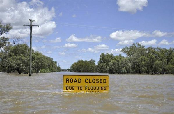 A flood warning sign starts to disappear below floodwaters near Charleville, about 685 km (426 miles) west of Brisbane February 6, 2012. Thousands of Australians were forced from their homes on Monday because of floods that have risen to record levels in some areas and killed one person, and authorities issued warnings for more than a dozen rivers in Queensland and New South Wales states. REUTERS/Queensland Police Service/Handout (AUSTRALIA - Tags: DISASTER ENVIRONMENT TPX IMAGES OF THE DAY) FOR EDITORIAL USE ONLY. NOT FOR SALE FOR MARKETING OR ADVERTISING CAMPAIGNS