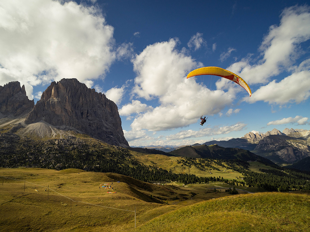 A paraglider breezes over a valley near the Puez Geisler Nature Park in northeast Italy near the Austrian border.  The sawtooth peaks are the Dolomites, part of the eastern Alps.
