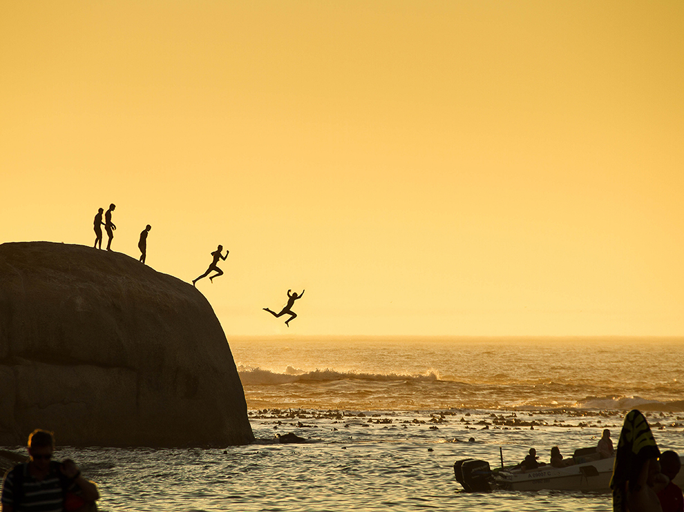 Boys in Clifton Beach in Cape Town, South Africa jumping into the Atlantic Ocean.  Photograph by Slawek Kozdras