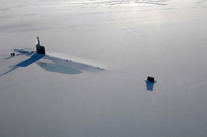 A submarine surfaces through arctic ice.