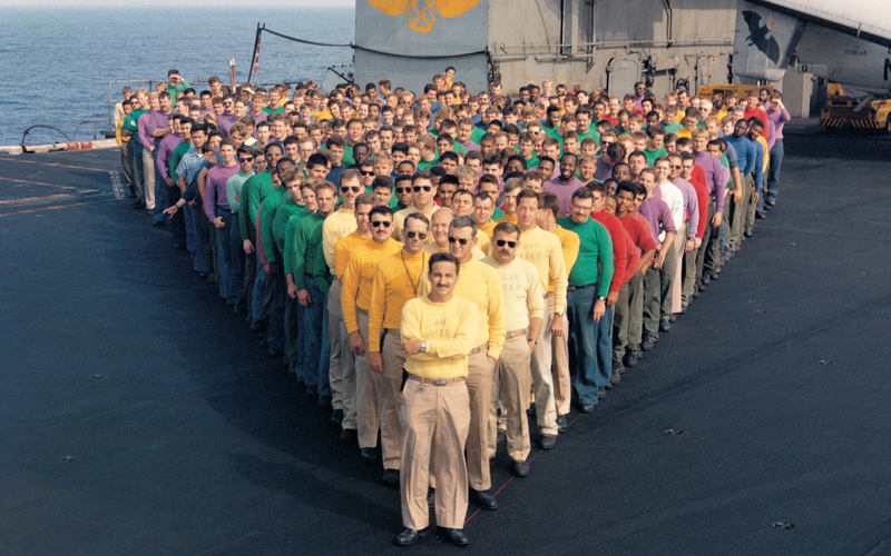 USS Coral Sea's air department Sailors, wearing the distinctive color jerseys that identify their carrier jobs,