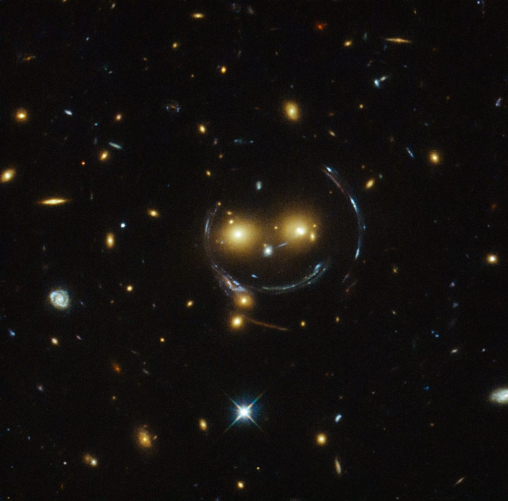"In this ""happy face"", the two eyes are actually very bright galaxies and the misleading smile lines are actually arcs caused by an effect known as strong gravitational lensing. Taken by the Hubble telescope and published by NASA."