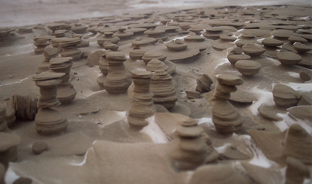 Cold and windy winter weather of the midwestern US has transformed frozen sand on the shore of Lake Michigan in St. Joseph, MI into a sea of tiny wind-sculpted towers. By Joshua Nowicki.