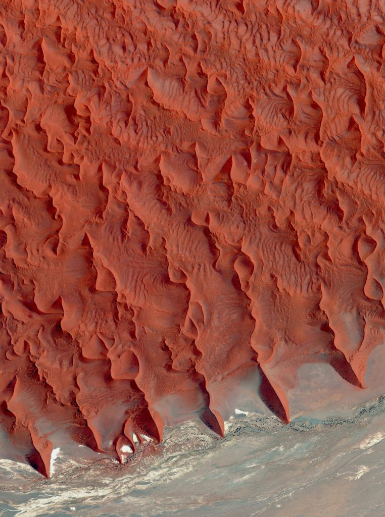 Sossusvlei is a salt and clay pan located on the edge of the Namib Desert in Namibia. These reddish sand dunes of the desert, seen in the top half of this Overview, are among the tallest in the world, with many rising more than 656 feet (200 meters.)