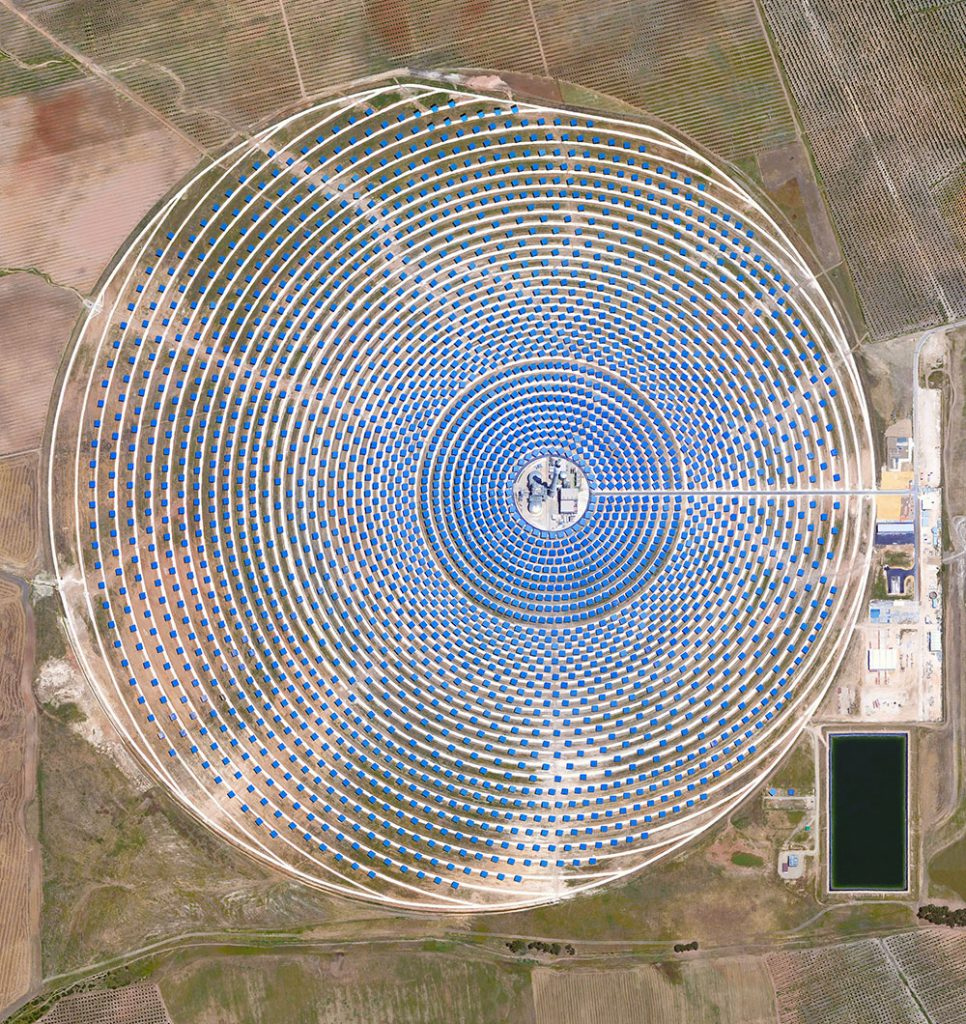 Gemasolar Thermosolar Plant in Seville, Spain. The solar concentrator contains 2,650 mirrors that focus the sun's thermal energy to heat molten salt flowing through a 140-metre-tall (460-foot) central tower. The molten salt then circulates from the tower to a storage tank, where it is used to produce steam and generate electricity.